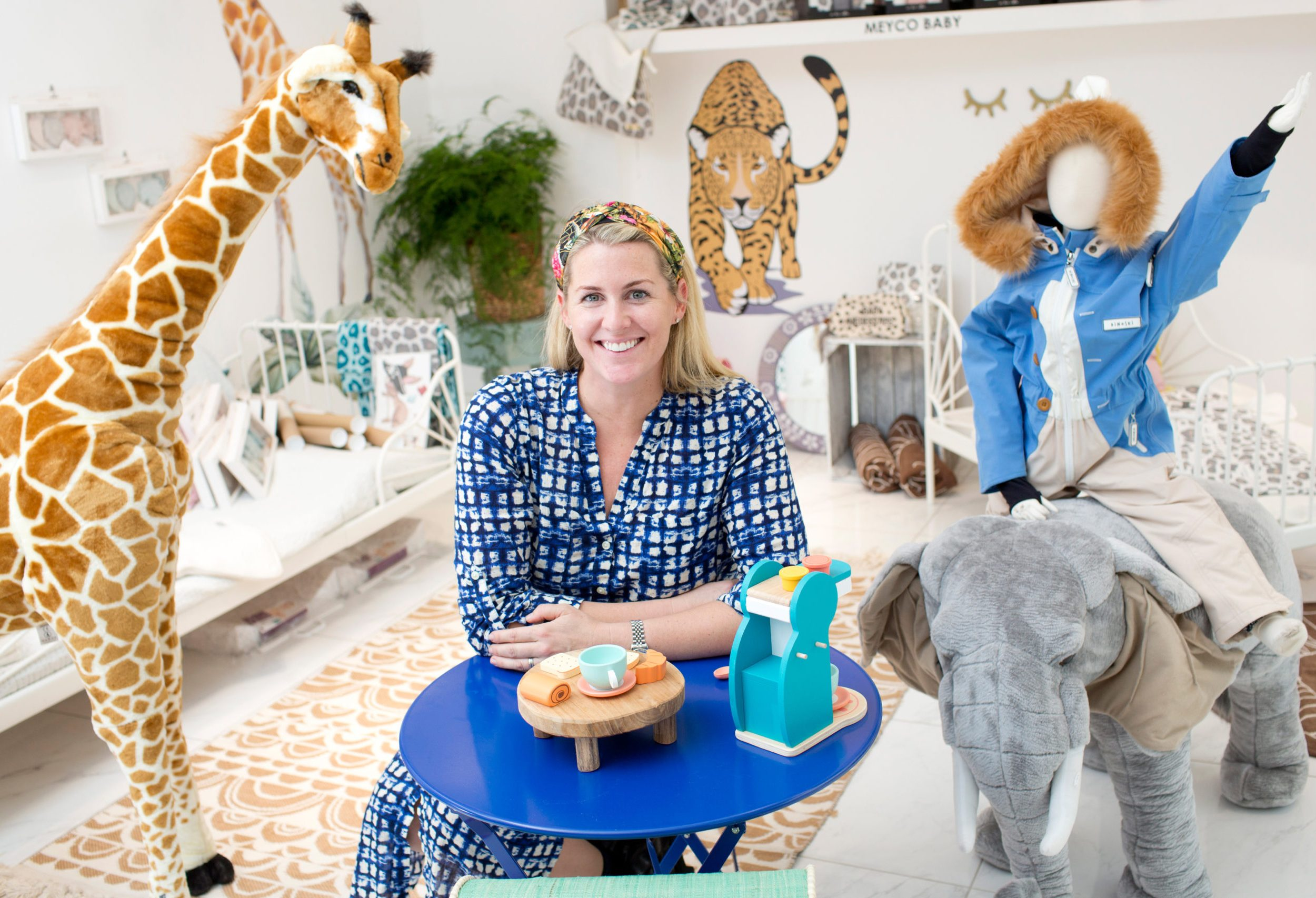 Woman sat at table surrounded by children's toys and furniture