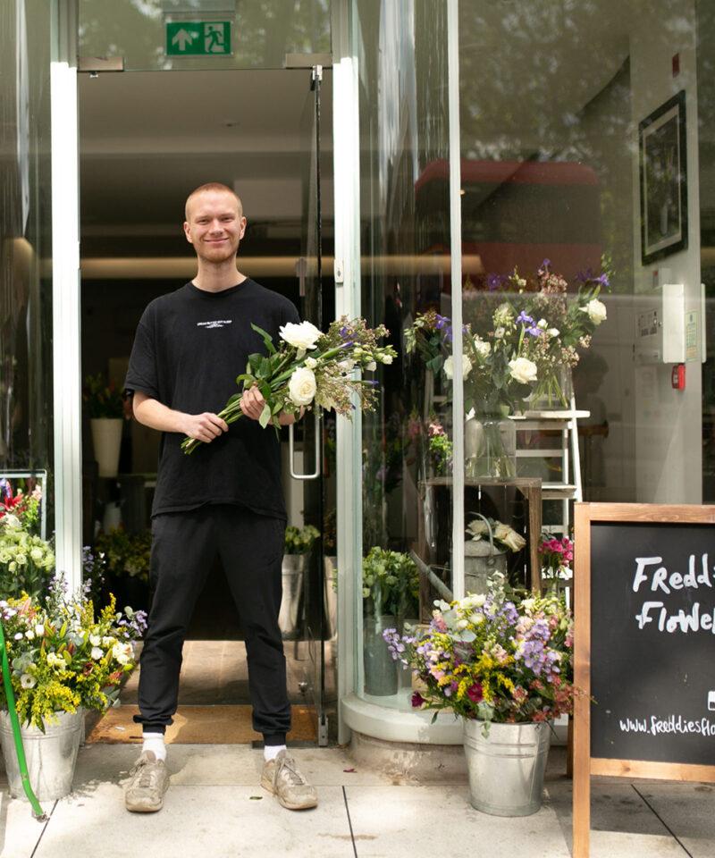 Freddie's flowers florist with Freddie outside holding flowers