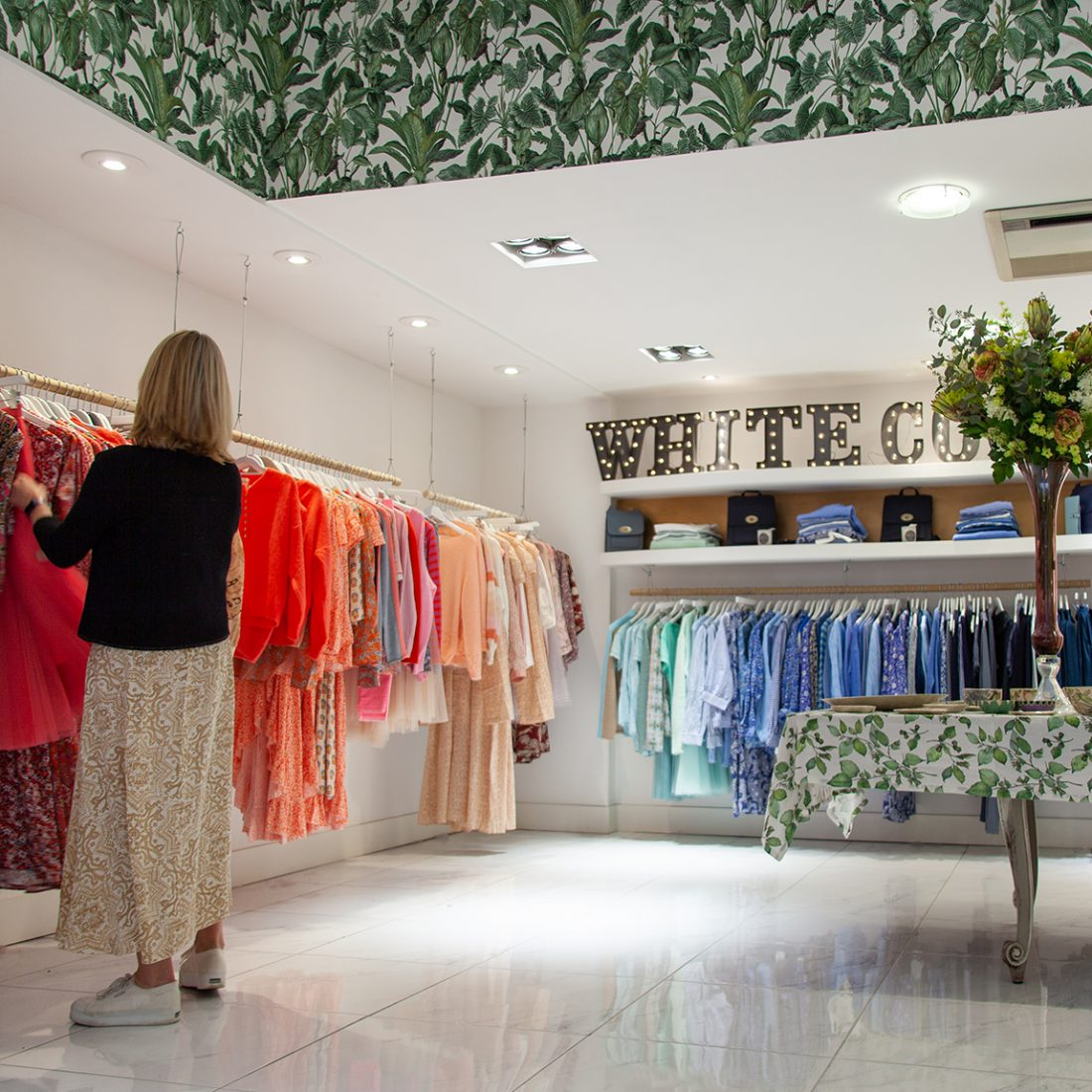 Interior of the White Coco clothes shop with brightly coloured women's clothes handing on rails, an illuminated sign for the shop and a woman browsing.