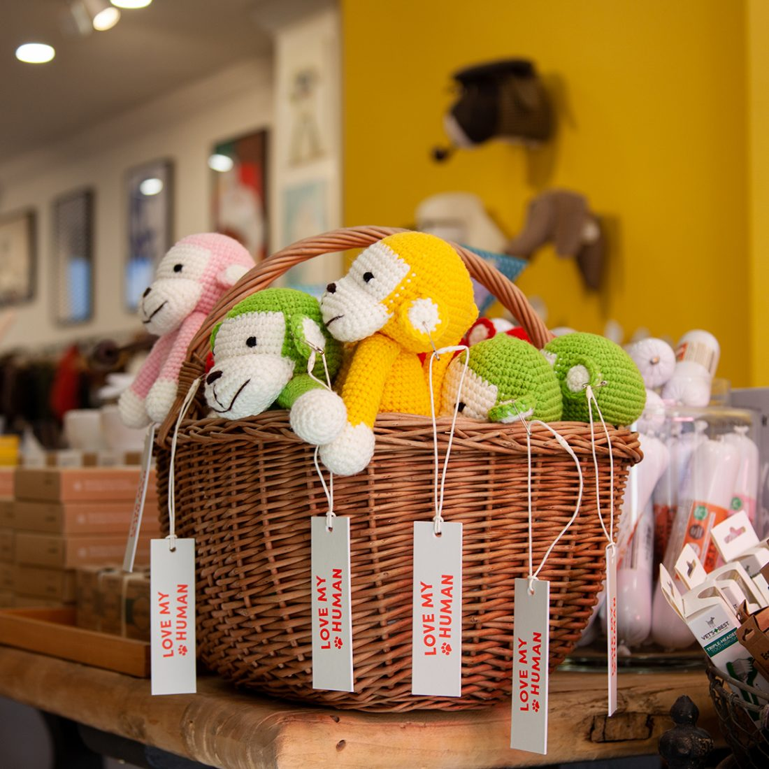 Basket of monkey themed dog toys and other dog accessories in the Love My human shop.