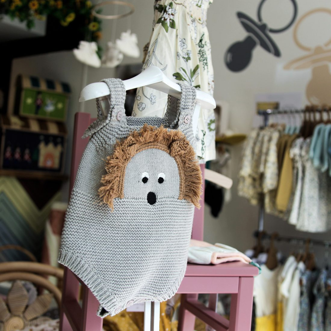 Interior of Nibbling shop in Chelsea - a cute child's romper with a hedgehog on and bright patterned children's clothing in the background