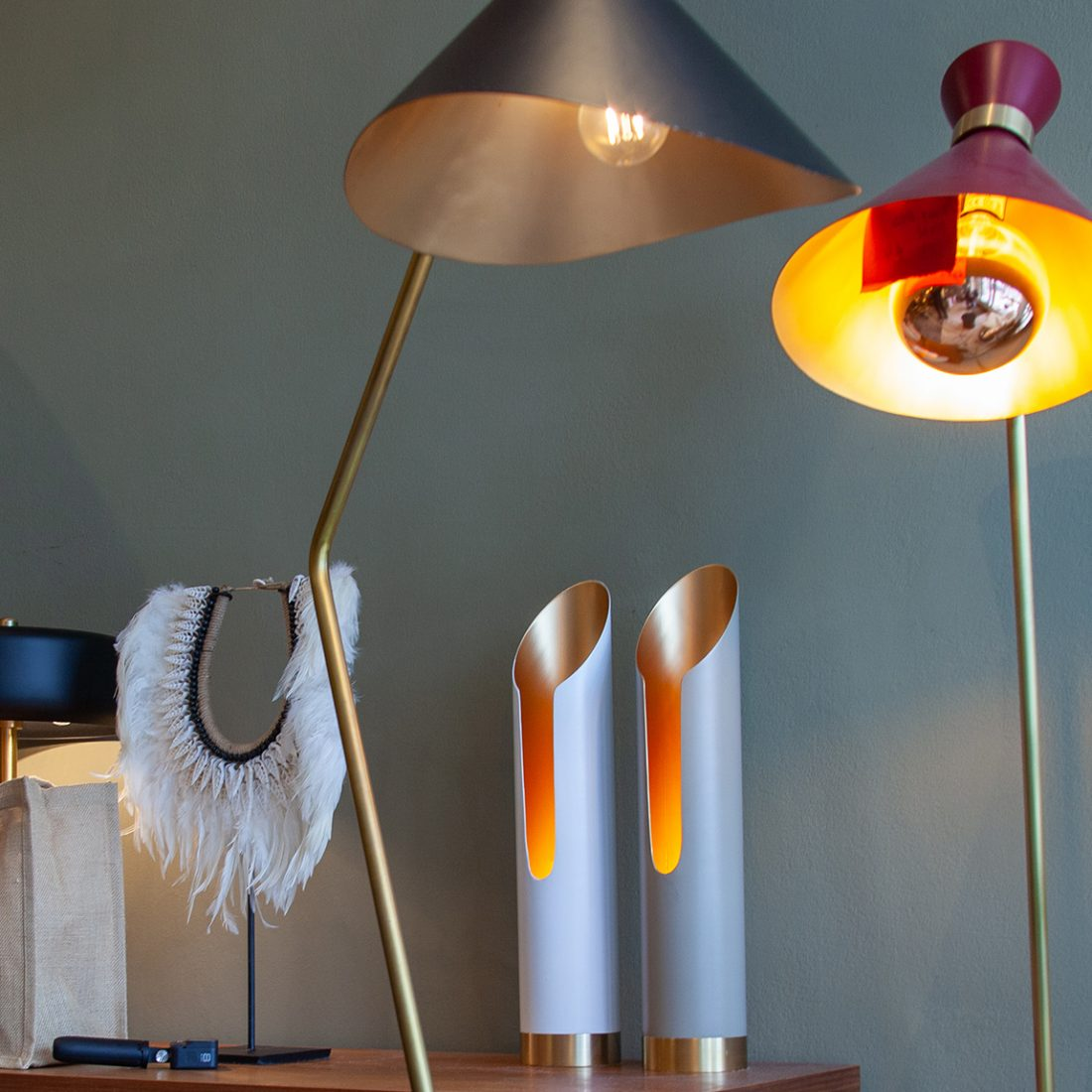 Modern standing lamp with red shade and gold inside alongside two pillar lamps with a warm lava glow and another feathered lamp at Gong Lighting.