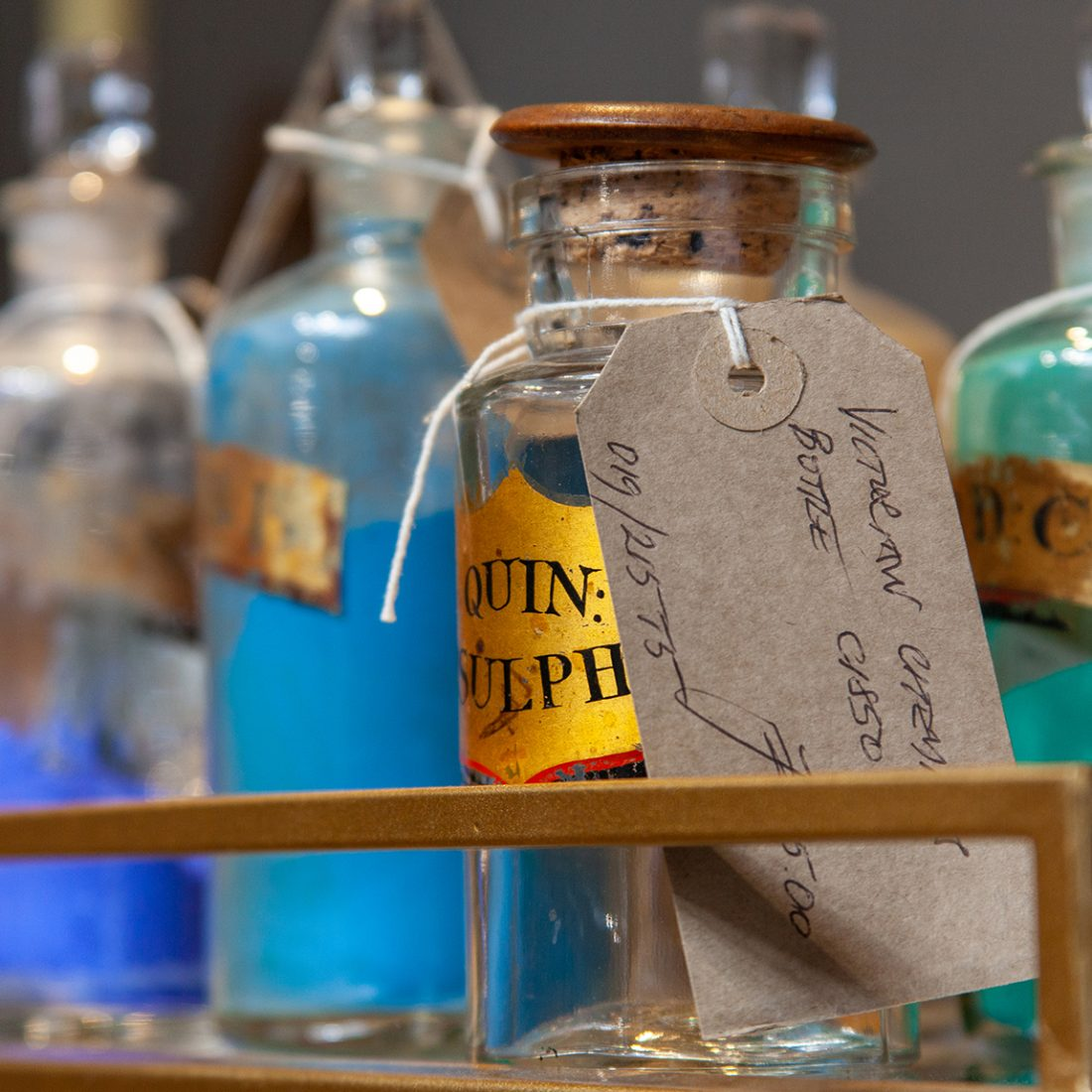 Small delicate victorian paint sulphate bottles in with gold labels and paper tags.