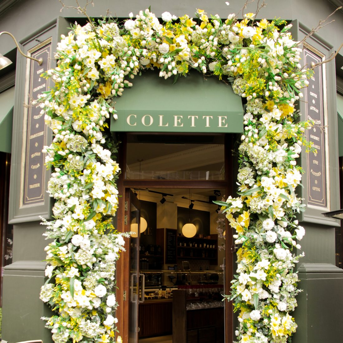 Bright yellow and green flower arch over the doorway of Colette restaurant and bar. The walls are a dark green and logo golden