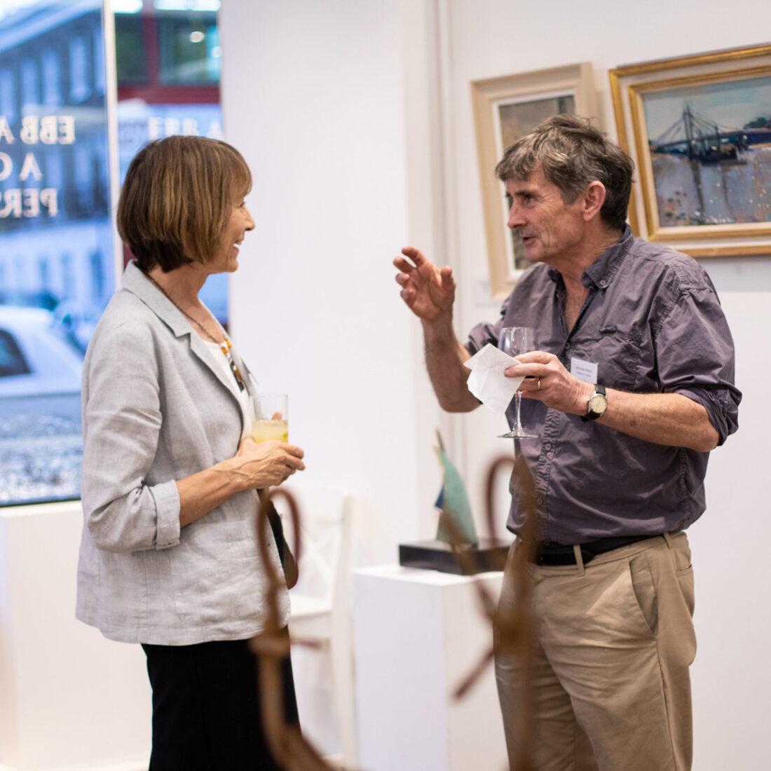 Man and woman talking inside art gallery